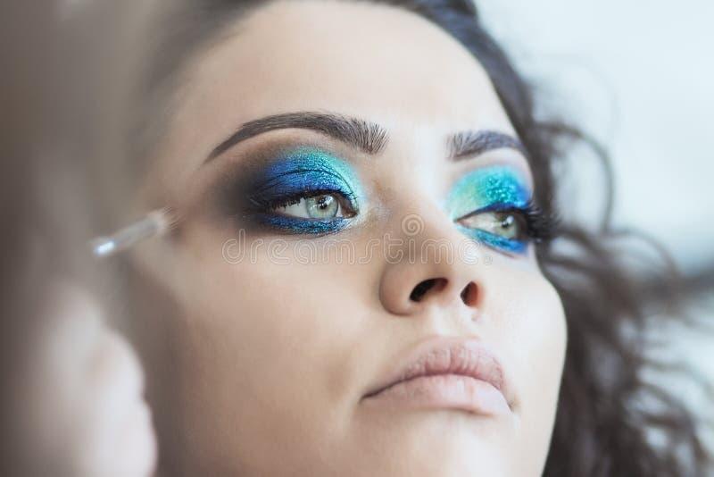 L'artiste de maquillage prépare le modèle pour le tir photos libres de droits