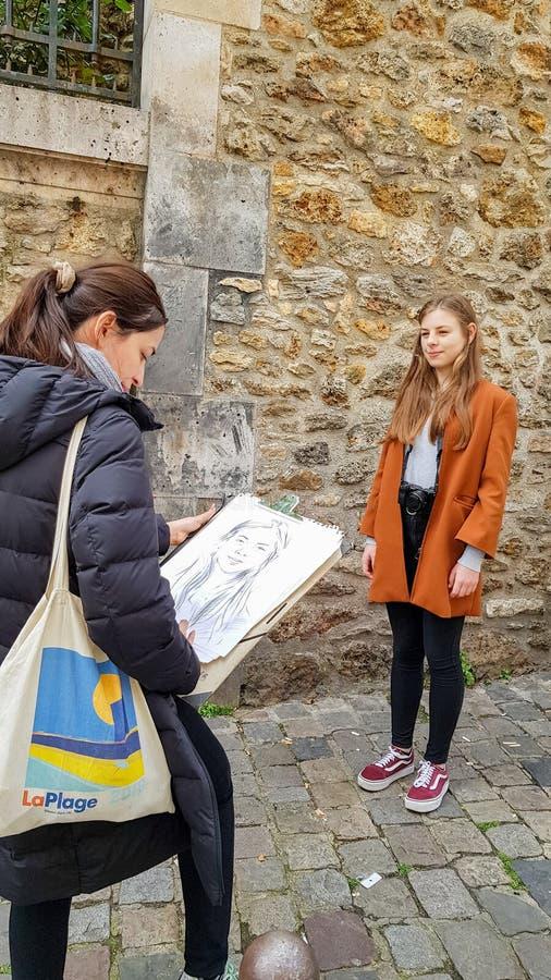 L'artiste de rue peint le portrait de la fille du Tertre en place dans Montmartre, Paris photos stock