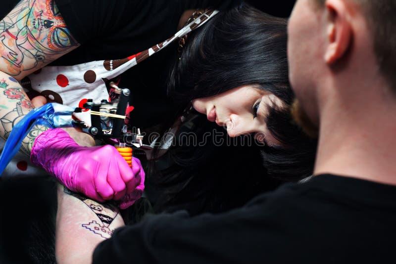 L'artiste de tatouage travaille à la convention de tatouage image libre de droits
