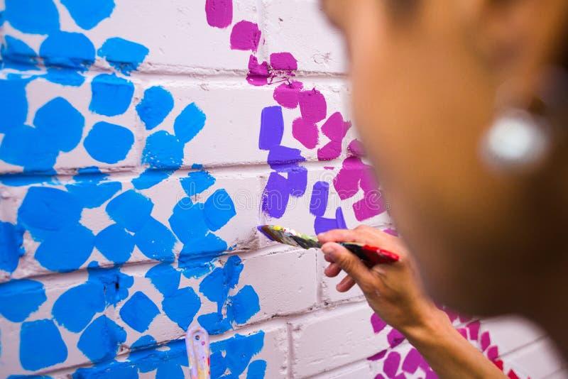 L'artiste dessine sur un mur de briques photo libre de droits