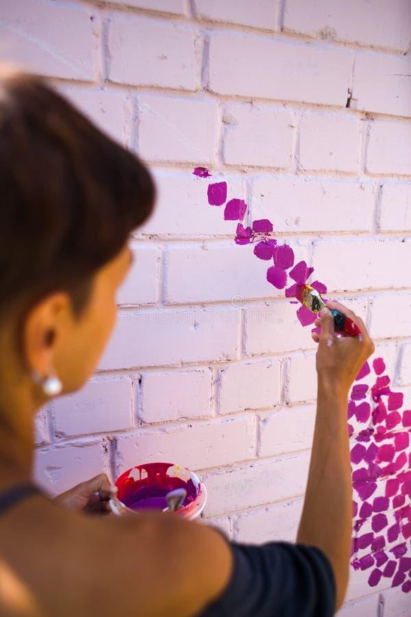 L'artiste dessine sur un mur de briques image libre de droits