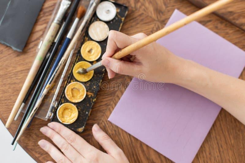 L'artiste dispose à travailler Applique la peinture à la brosse Plan rapproch? L'atmosphère de l'atelier créatif photos stock