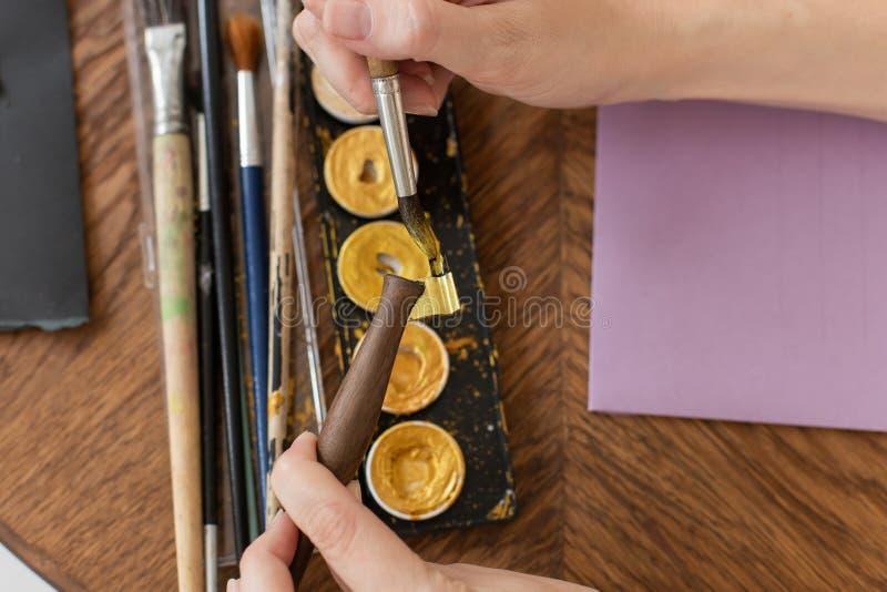 L'artiste dispose à travailler Applique la peinture à la brosse Plan rapproch? L'atmosphère de l'atelier créatif photo libre de droits