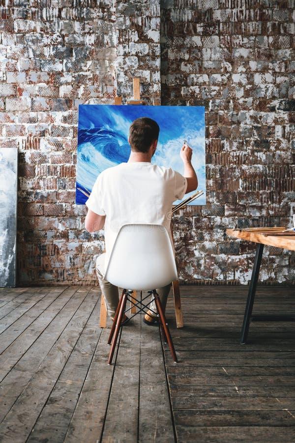 L'artiste est peinture par peinture à l'huile dans le studio d'art tout en se reposant sur une chaise devant une toile Processus  images stock