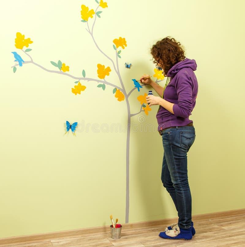 L'artiste féminin dessine l'arbre, les papillons et les oiseaux sur le mur image stock