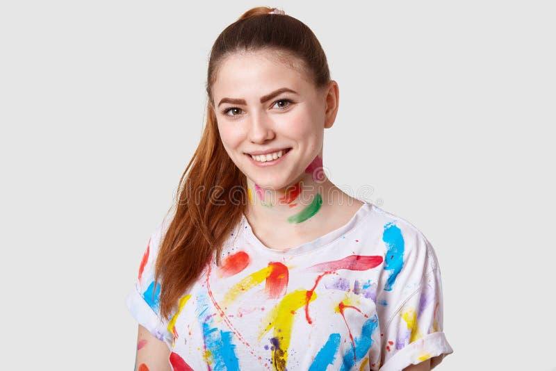 L'artiste féminin européen heureux joyeux a la queue de poney, sourire toothy, montre même les dents blanches, habillées dans le  photos stock