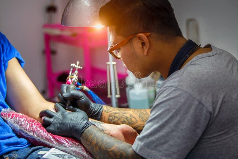 L'artiste haut de tatouage de fin démontre le processus d'obtenir le tatouage noir avec la peinture photos libres de droits