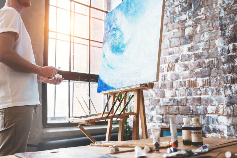 L'artiste se tient devant le chevalet avec une toile et considère son travail Peintre dans le studio d'art Passe-temps et escroqu photographie stock libre de droits
