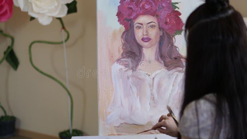 L'artiste tire un portrait de la nature l'artiste dessine des détails du visage modèle du ` s sur la toile avec une brosse et des image libre de droits