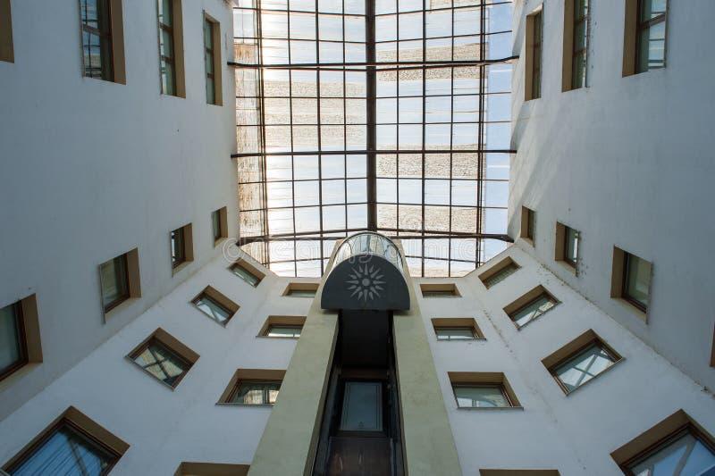 L'ascenseur de rue dans le bâtiment se lève jusqu'au dessus, entouré par des fenêtres images libres de droits