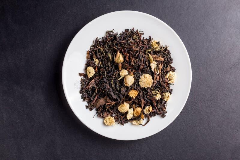 L'asiatico del tè fiorisce il oolong sul piatto bianco su backgroung scuro fotografia stock libera da diritti