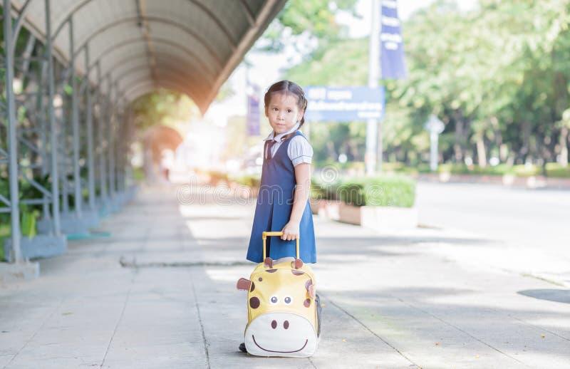 L'asiatico sveglio con la borsa e aspetta di nuovo alla scuola immagine stock libera da diritti