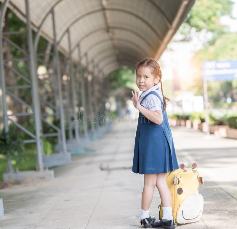 L'asiatico sveglio con la borsa e aspetta di nuovo alla scuola immagini stock libere da diritti