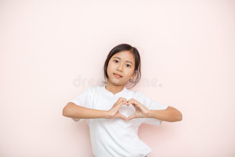 L'Asiatique a bronzé le portrait d'enfant de fille de peau au-dessus du fond rose de mur, photos stock