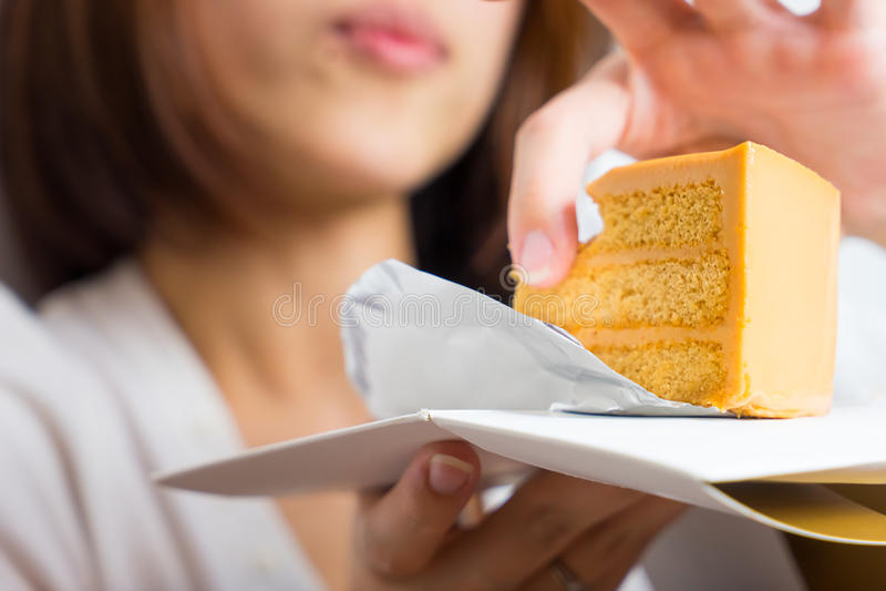L'Asiatique féminin mange le gâteau de caramel avec la main photos libres de droits