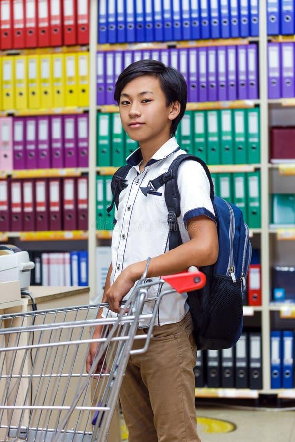 L'Asiatique un de sac à dos de boutique d'achats de chariot à garçon fournit le compteur de papeterie de globe de supermarché d'a photo libre de droits