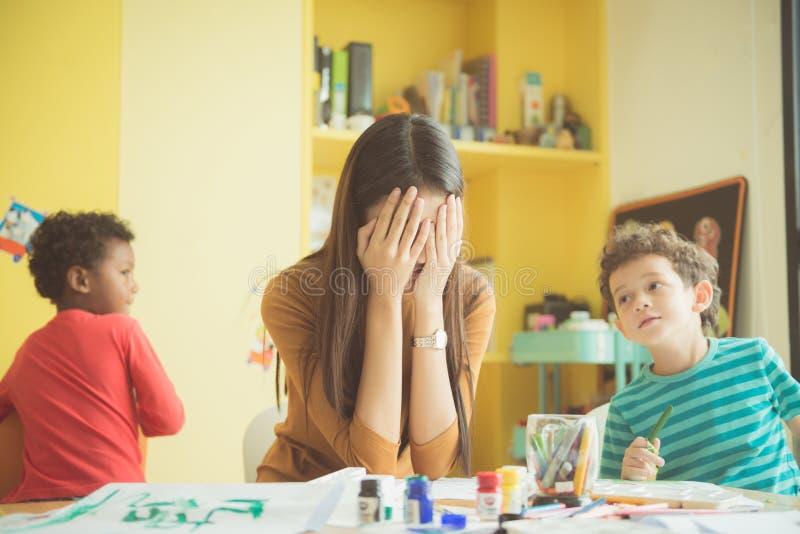 L'asilo asiatico dell'insegnante passa chiuso entrambe le orecchie lei in un ribaltamento del non riuscito di ad acquietare imper fotografia stock