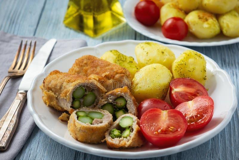 L'asparago arrostito ha farcito il filetto di carne di maiale servito con le patate ed i pomodori fotografia stock libera da diritti