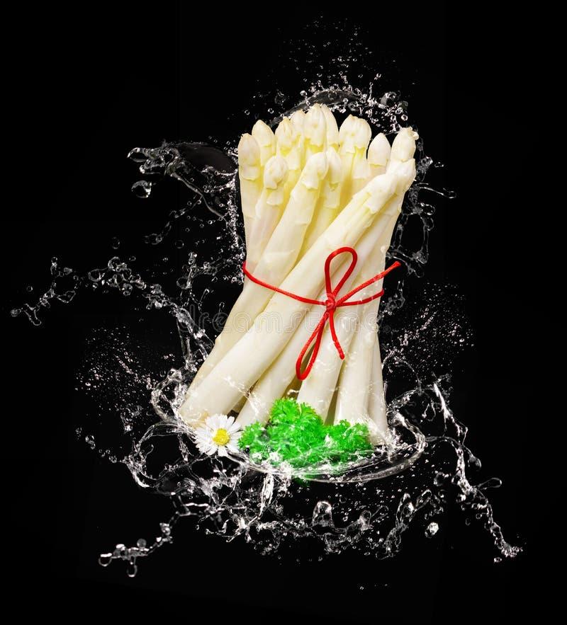 L'asparago fresco cade nell'acqua immagine stock libera da diritti