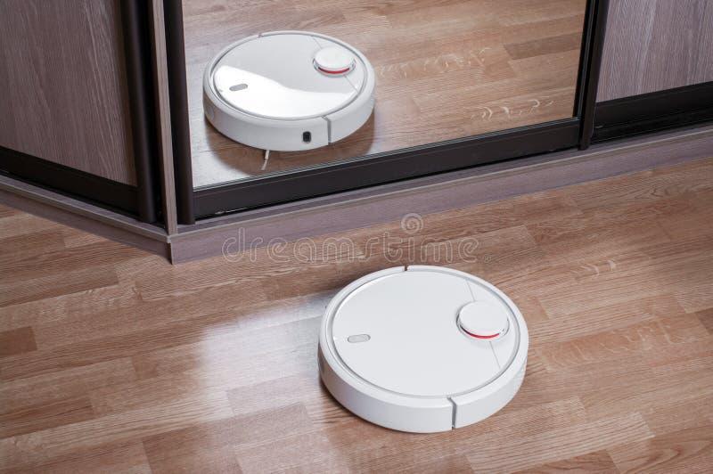 L'aspirapolvere del robot sul pavimento laminato è riflesso in specchio del guardaroba, robotica che domestica astuta la pulizia  immagine stock libera da diritti