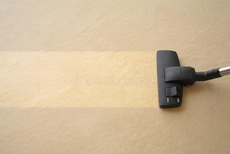 L'aspirateur nettoie le tapis photographie stock libre de droits