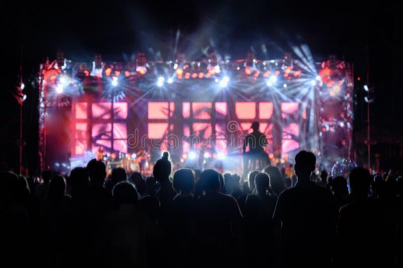L'assistance de la jeunesse de silhouette observent le concert de nuit photos stock