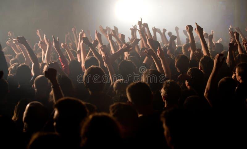 L'assistance a soulevé leurs mains au concert photos stock