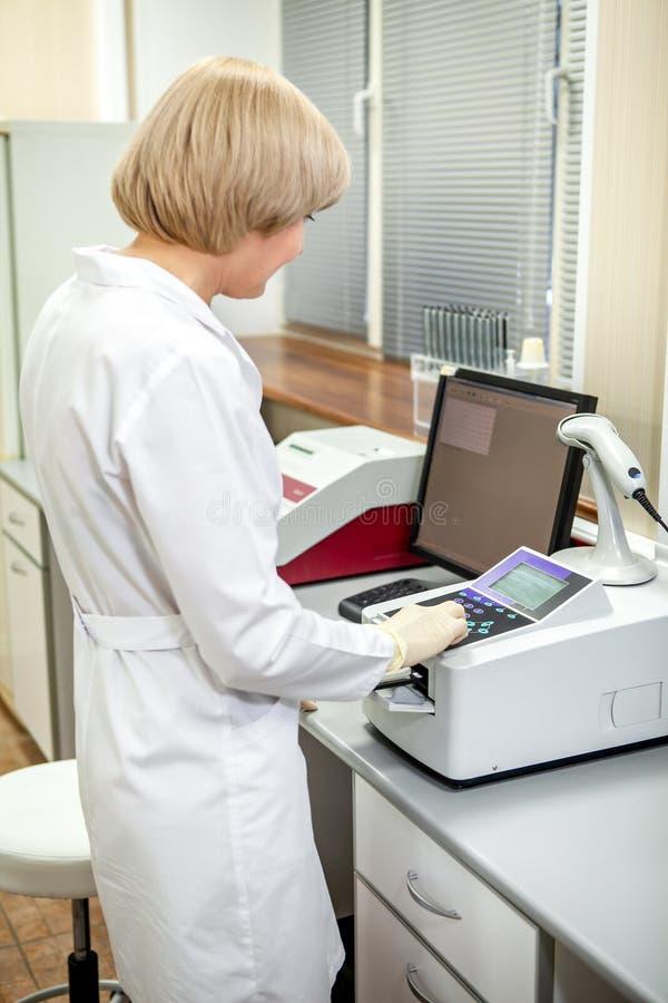 L'assistant de laboratoire sélectionne le mode de fonctionnement de l'appareil pour analyser des échantillons images libres de droits