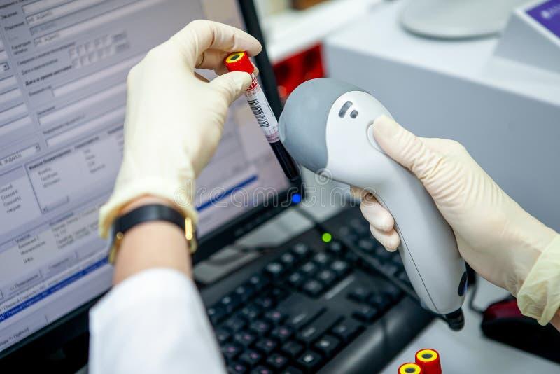 L'assistant de laboratoire tient l'échantillon dans sa main et saisit les données de l'échantillon utilisant un lecteur de code b photo stock
