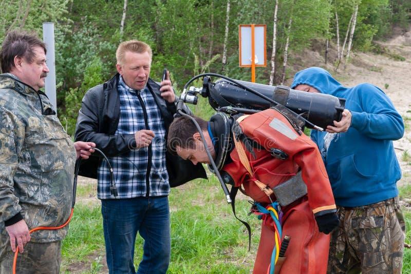 L'assistente aiuta l'operatore subacqueo a mettere sopra un pallone con l'aria compressa immagine stock libera da diritti