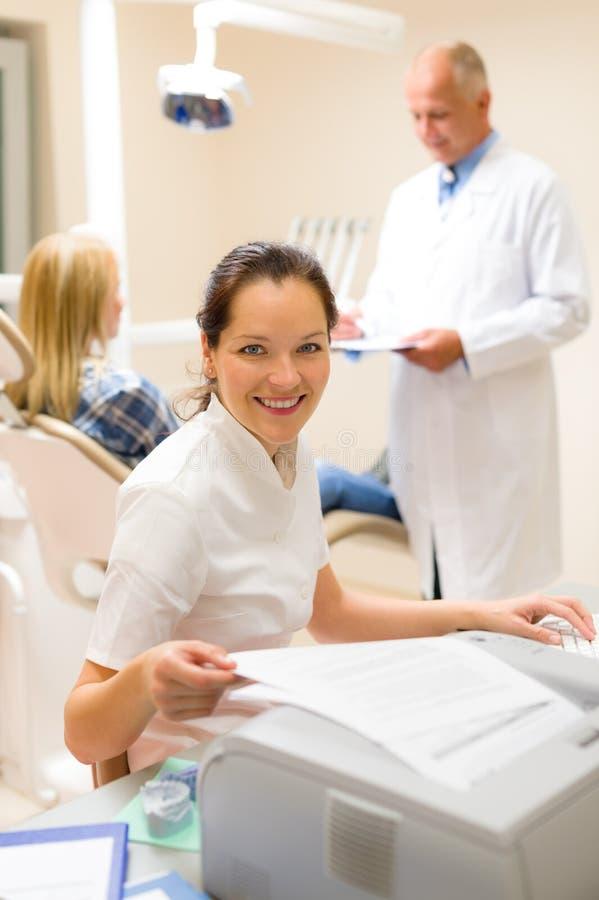 L'assistente dentale redige il documento personale paziente immagini stock