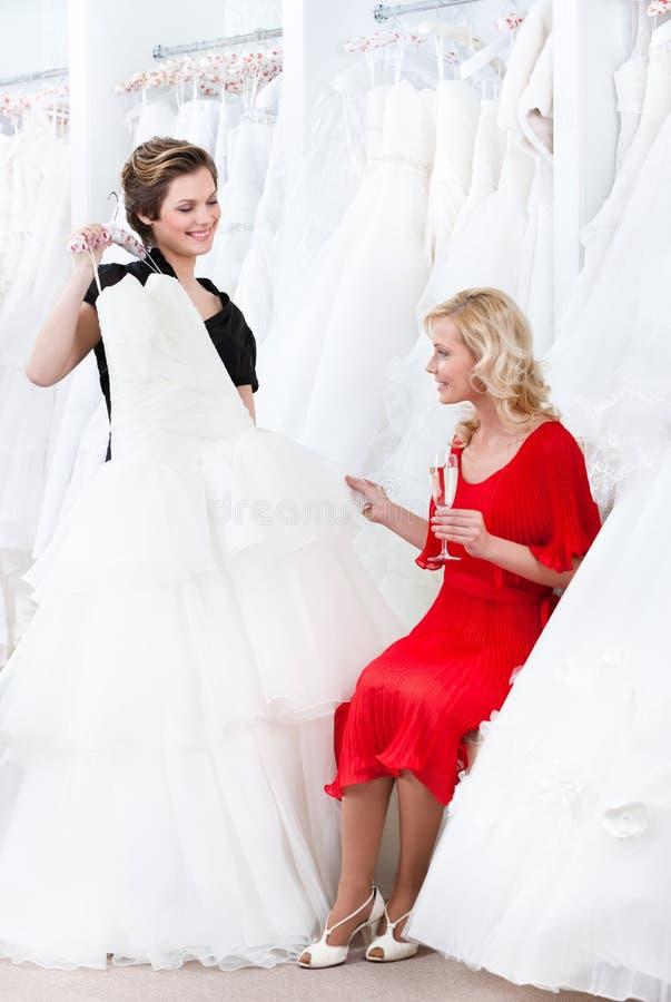 L'assistente di negozio propone un altro vestito alla sposa fotografia stock libera da diritti
