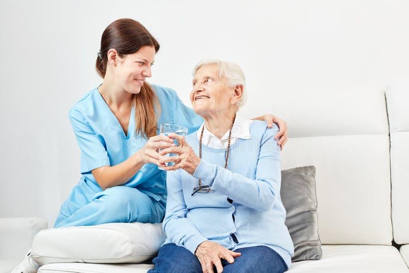 L'assistente di professione d'infermiera d? ad anziano un bicchiere d'acqua immagini stock libere da diritti