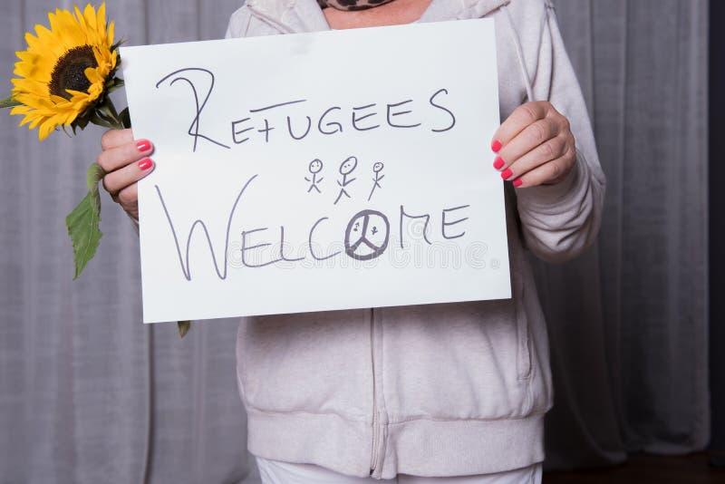 L'assistente femminile accoglie favorevolmente i rifugiati con il girasole immagini stock libere da diritti