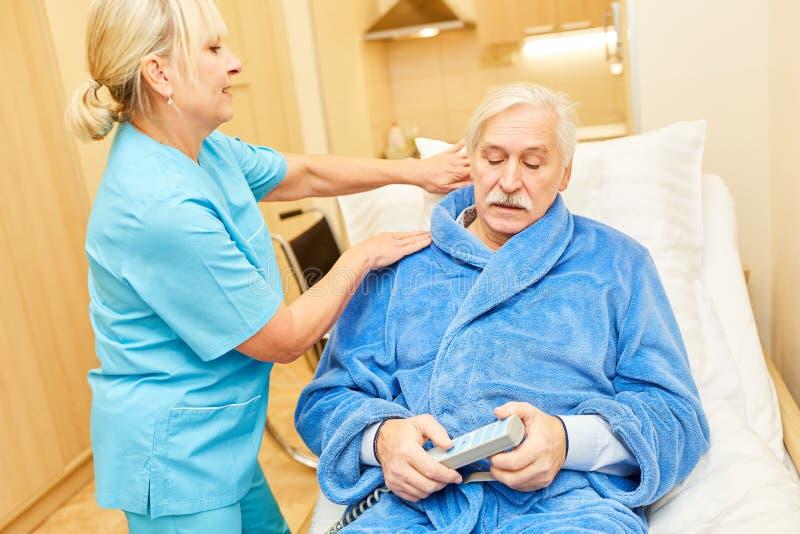 L'assistenza di cura si occupa di un anziano malato immagine stock