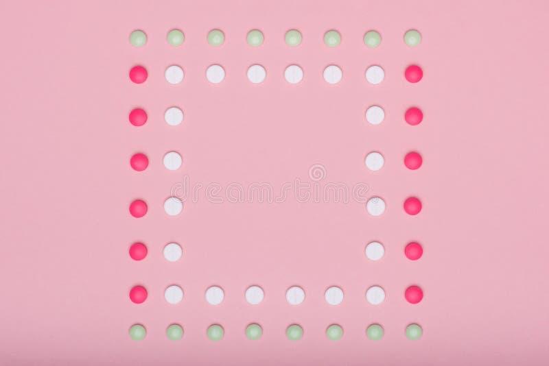 L'assortiment de diverses pilules colorées dans une rangée, d'isolement sur le pastel rose a coloré le fond Pilules de médicament images stock