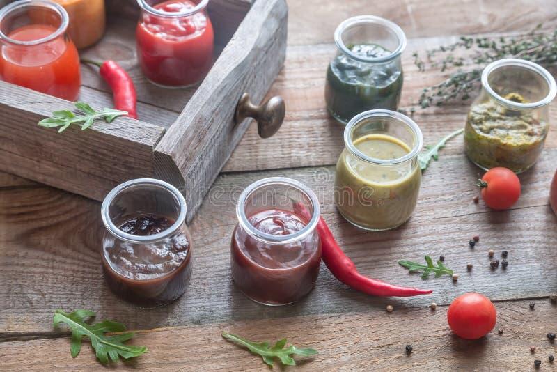L'assortiment des sauces dans le verre cogne avec des ingrédients images stock