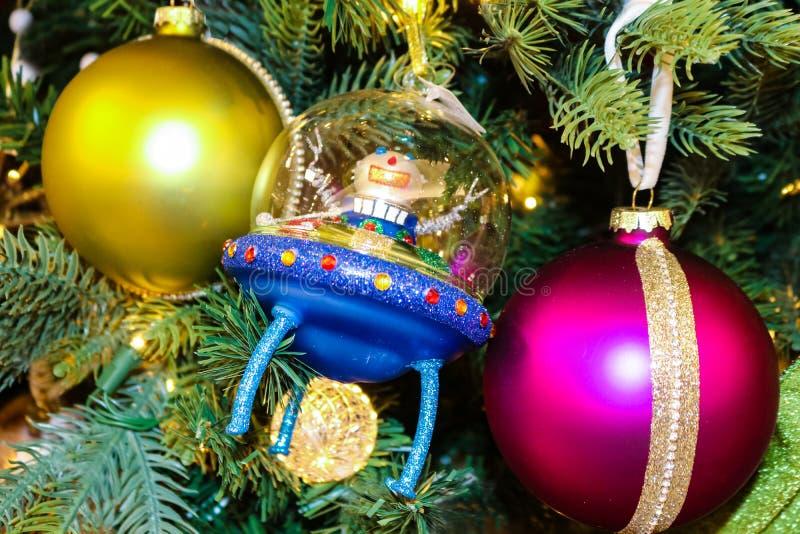 L'astronauta che dà la pace firma dentro il razzo straniero blu sull'albero di Natale tradizionale con gli ornamenti rossi e mage immagini stock libere da diritti