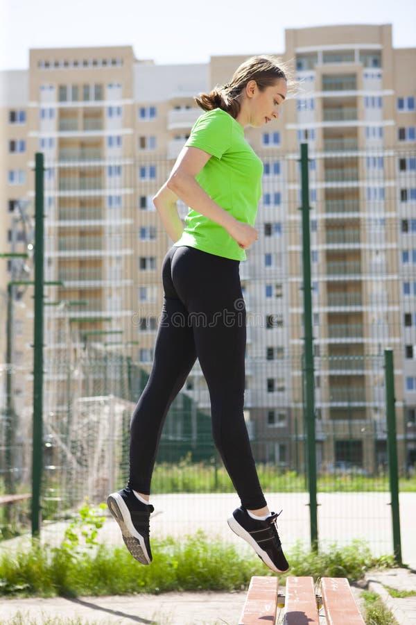 L'athlète courante adaptée de jeune fille vole par l'air tandis que le fonctionnement fait une ficelle dans le ciel faisant une c photo libre de droits