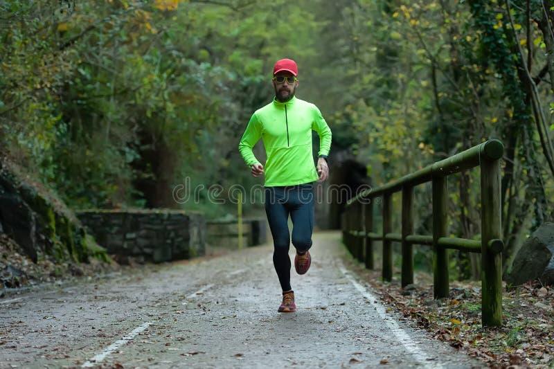 L'athlète d'homme court sur la voie pour bicyclettes en automne images stock