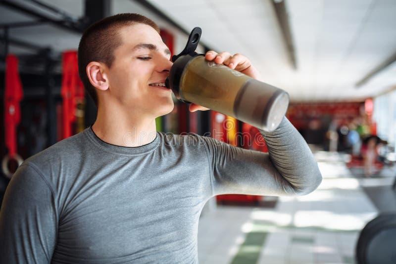L'athlète d'homme a fait une pause en formation et eau potable, avec une bouteille de sports dans le gymnase photo stock