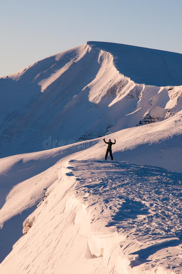 L'athlète de fille se tient avec ses mains dans les montagnes en hiver photo stock