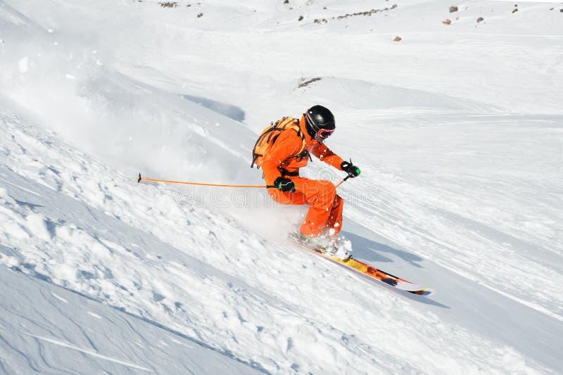 L'athlète de ski dans une poudre fraîche de neige se précipite en bas de la pente de neige photographie stock libre de droits