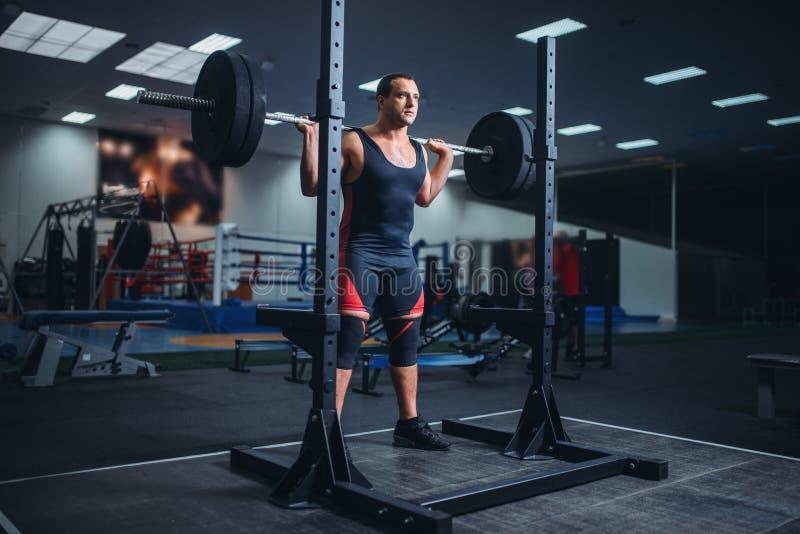 L'athlète dispose à faire des postures accroupies avec le barbell photo libre de droits