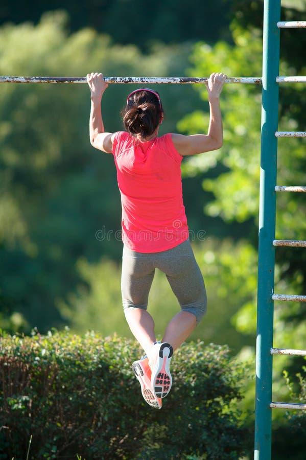L'athlète fort de femme est Chin-UPS et des Pullups s'exerçant sur un aban photo libre de droits