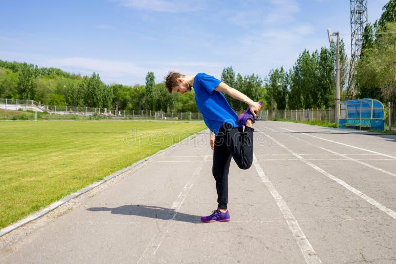 L'athlète masculin concentré extérieur étirant son corps dans faire de vêtements de sport sain pratique images stock