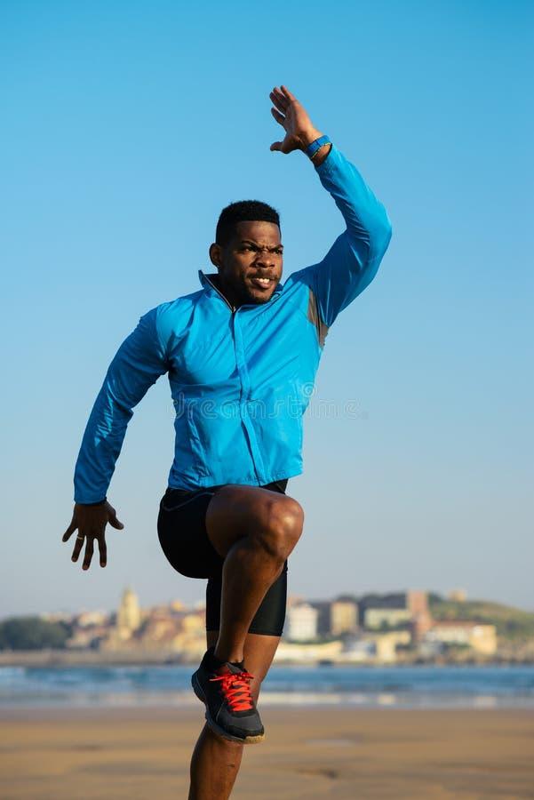 L'athlète noir faisant la puissance saute avant le fonctionnement photographie stock