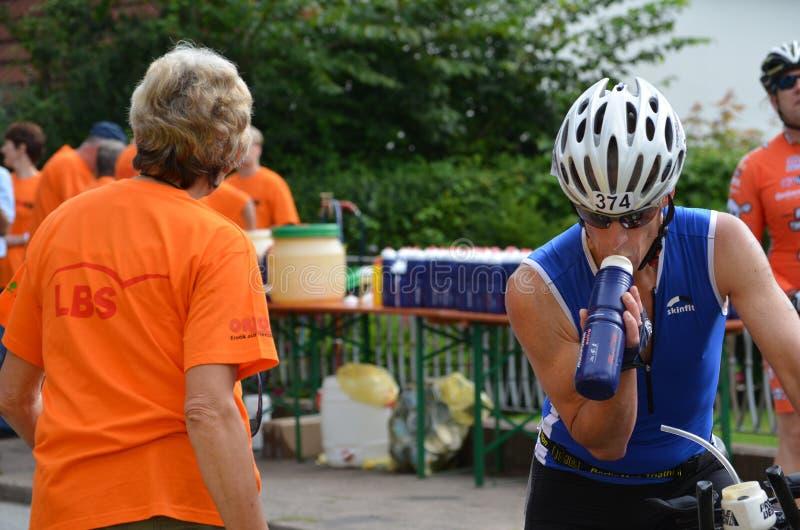 L'athlète reçoit la boisson d'énergie à un événement de triathlon photographie stock