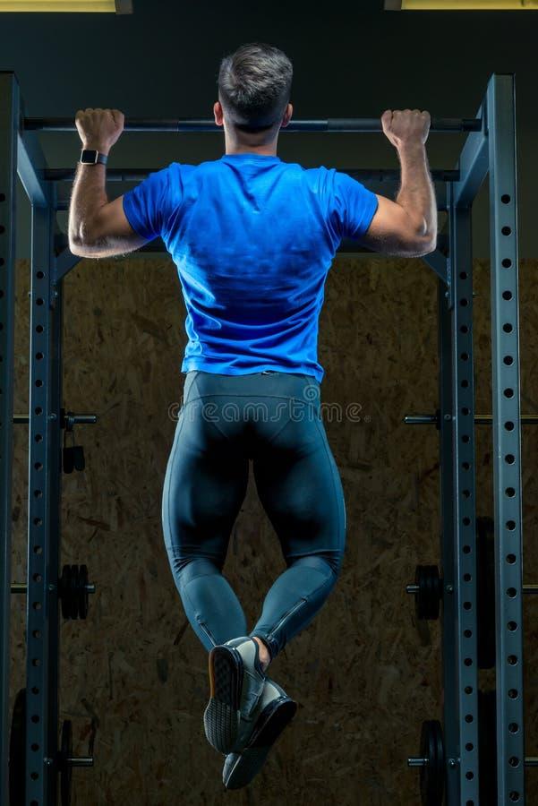 L'athlète se tire sur la barre dans la vue de gymnase du photographie stock libre de droits