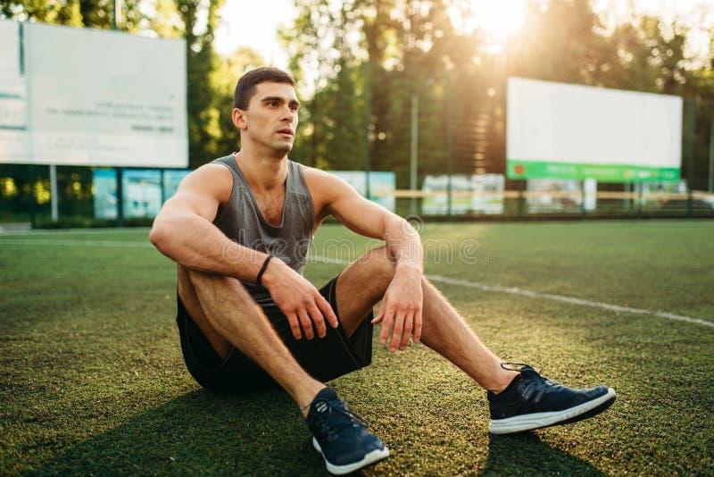 L'athlète tient la bouteille de l'eau, séance d'entraînement extérieure image libre de droits